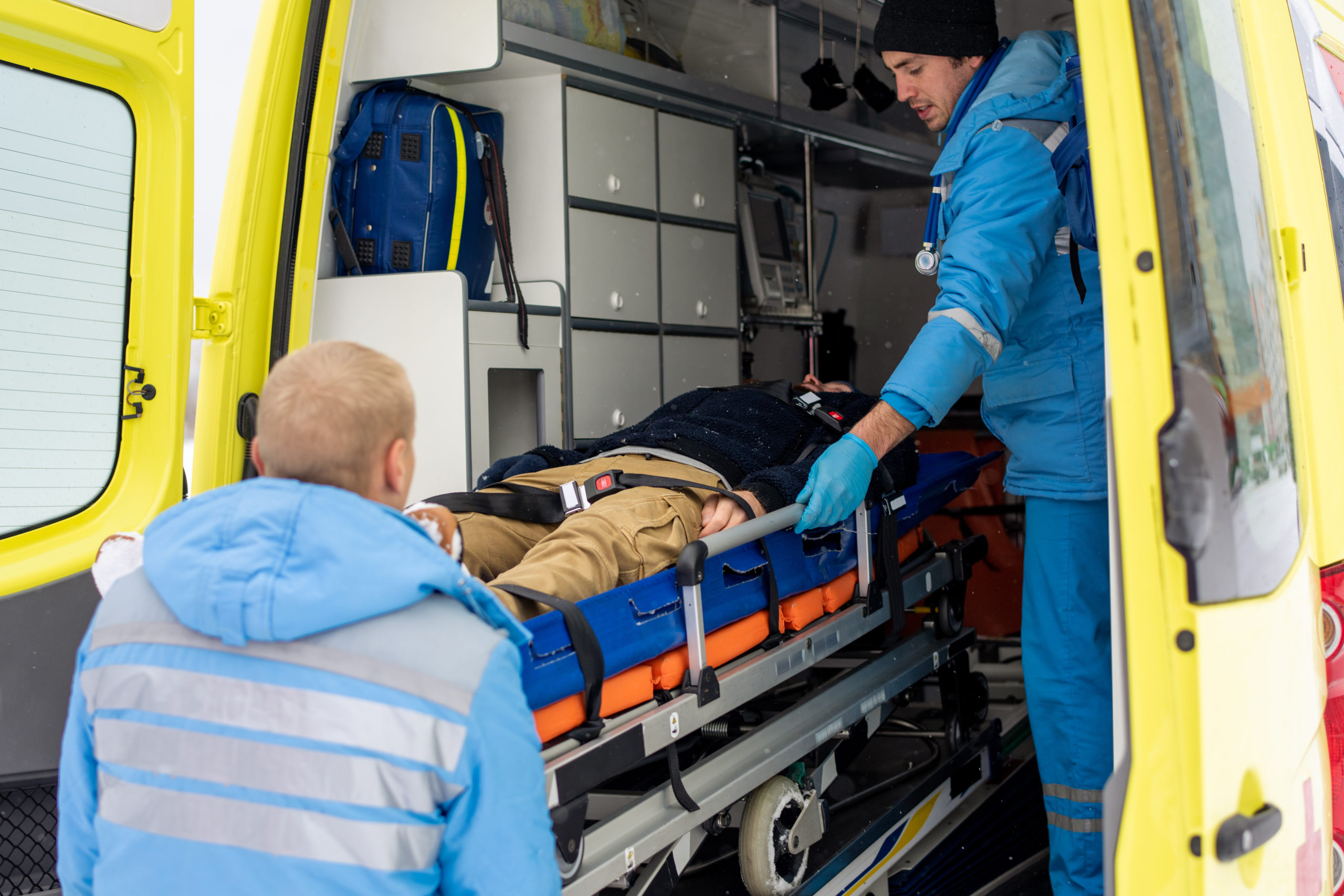 Paramedics in uniform pushing stretcher with fixed unconscious man into ambulance car to get him to hospital