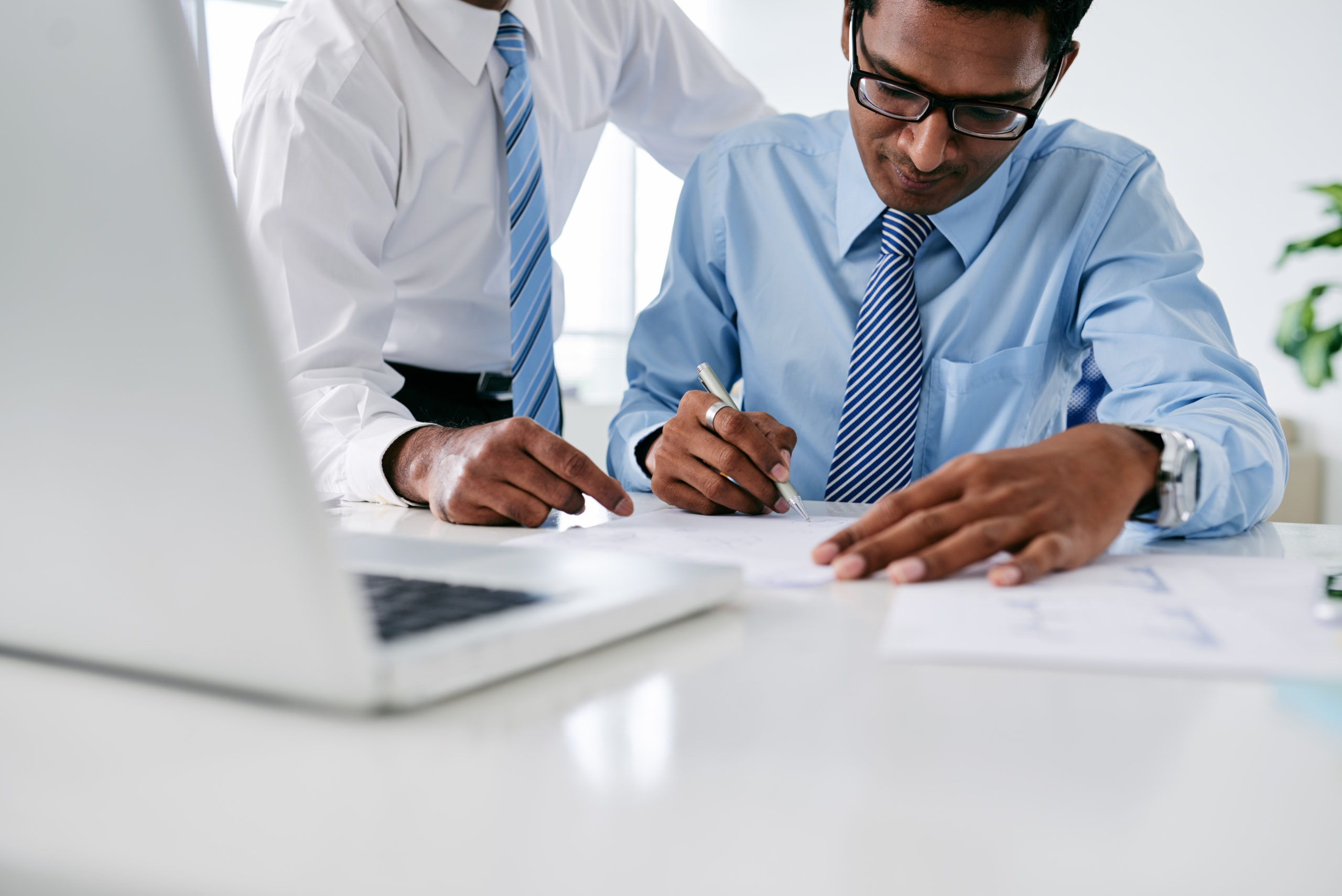 Colleagues signing contract at table in office